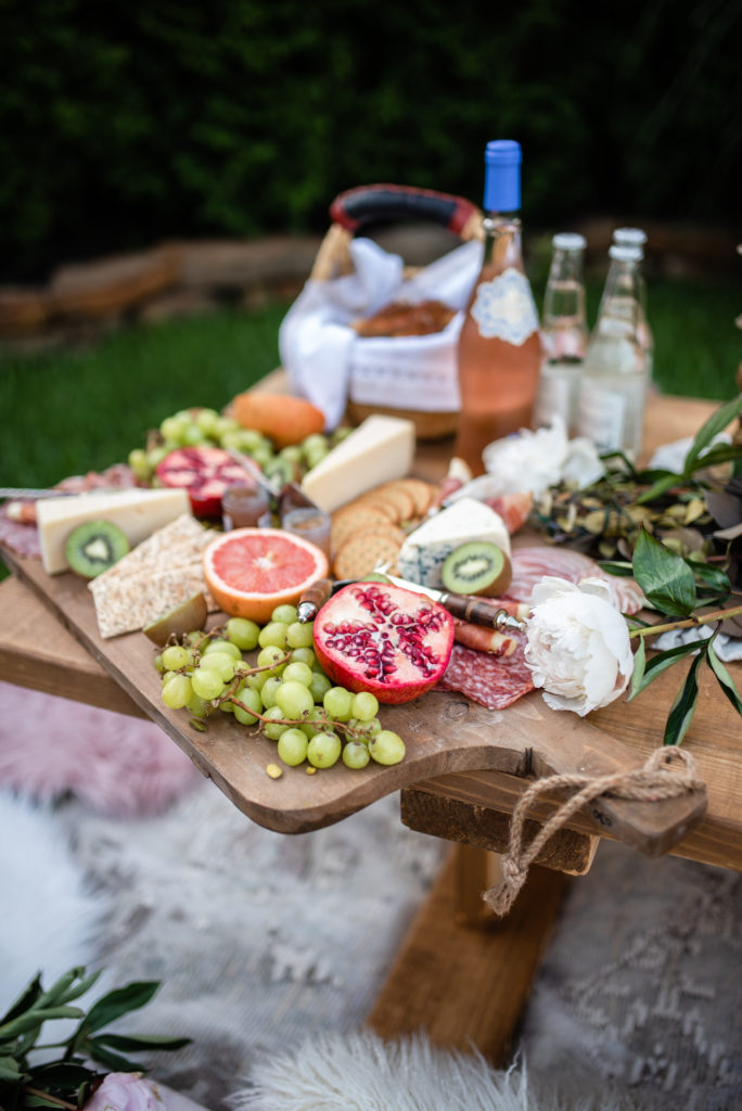 charcuterie board with pomegranate grapefruit and kiwi